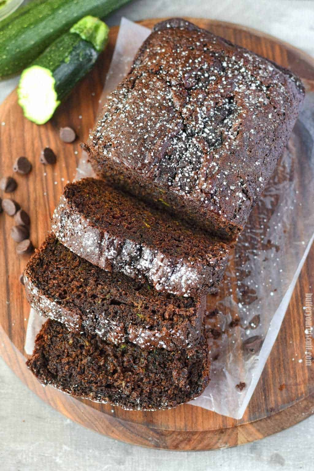 chocolate zucchini bread sliced on a cutting board with chocolate chips