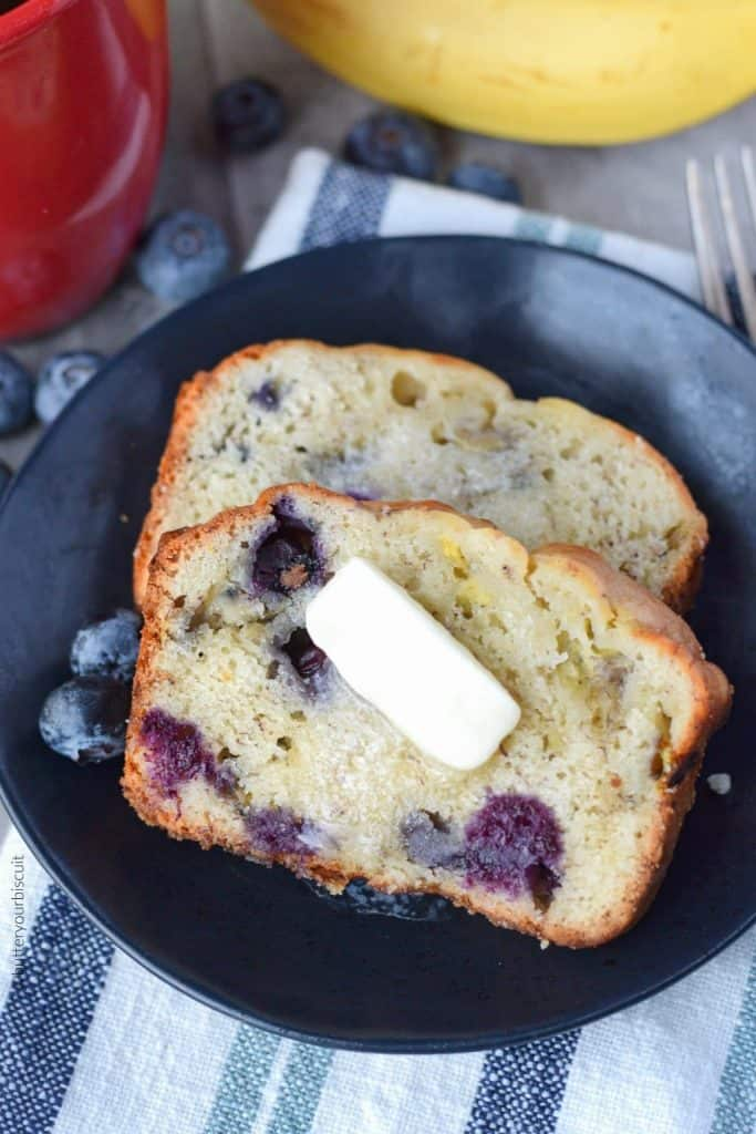 Banana Blueberry cream cheese bread on a black plate with a dab of melted butter