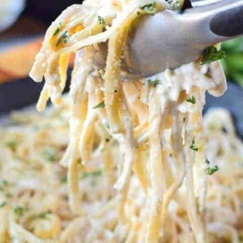 garlic fettuccine alfredo in a cast iron skillet with tongs picking up a scoop