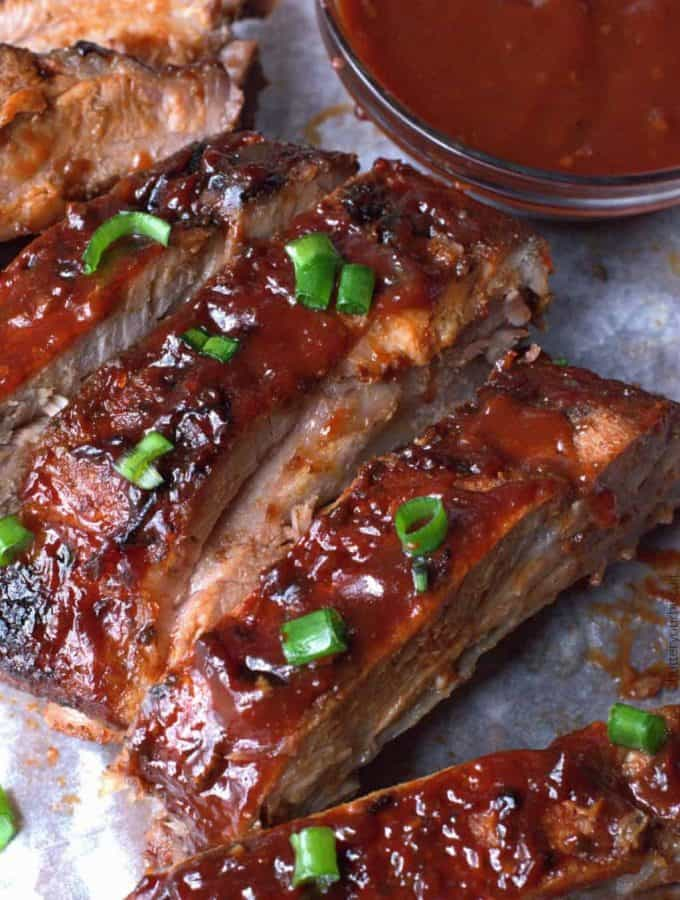 Easy oven BBQ baked ribs cut and placed on a sheet pan with a side of barbecue sauce