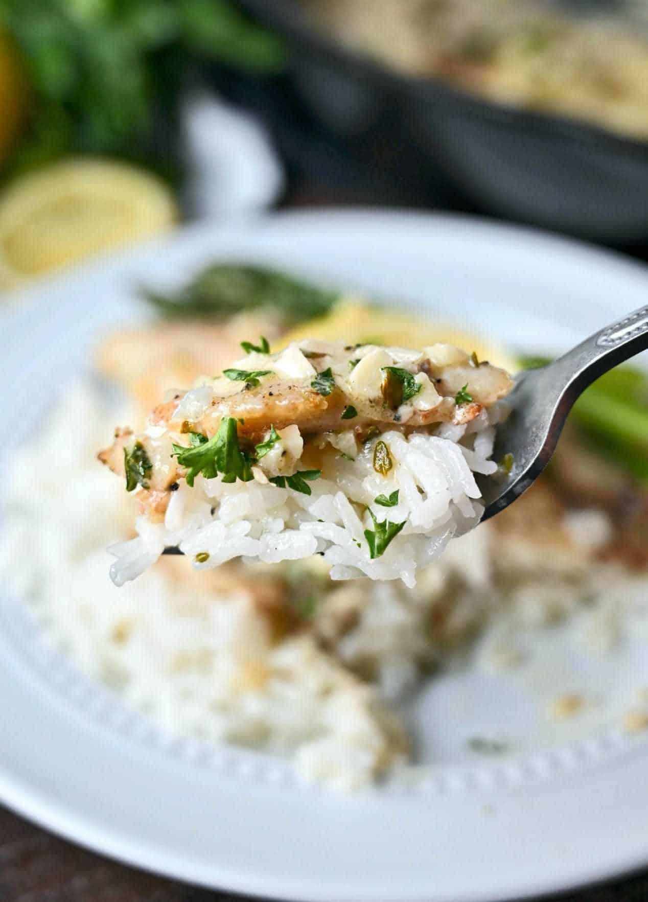 O mușcătură de orez alb și tilapia pe o furculiță.