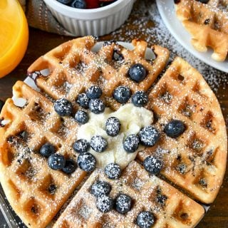 blueberry waffle on a plate with fresh blueberries, butter and powdered sugar on top.