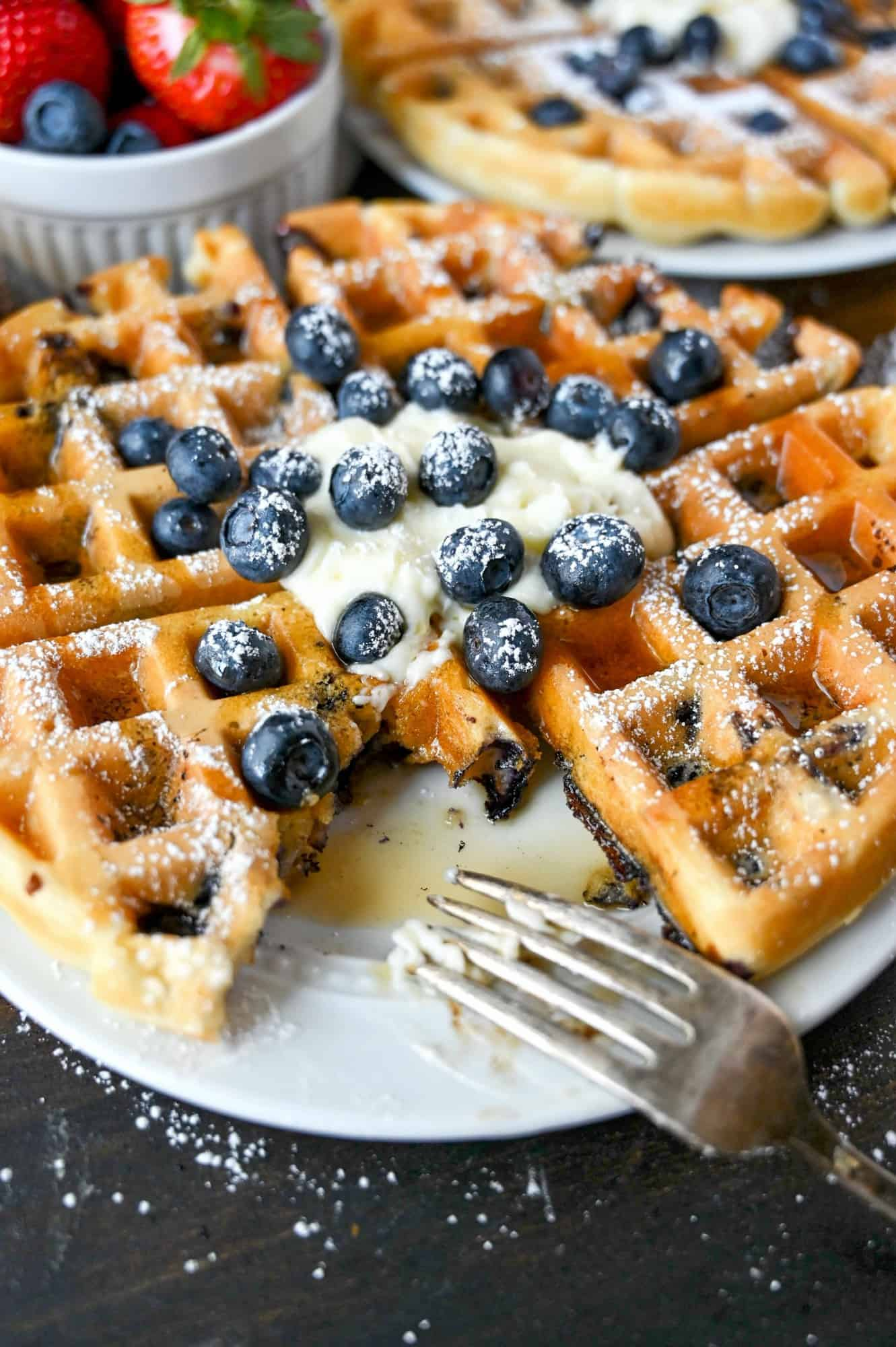 Blueberry waffle on a plate with a bite missing.
