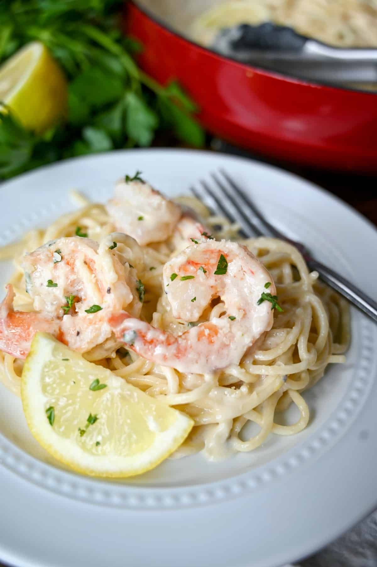 Close up shot of shrimp pasta. lemon slice and a fork.