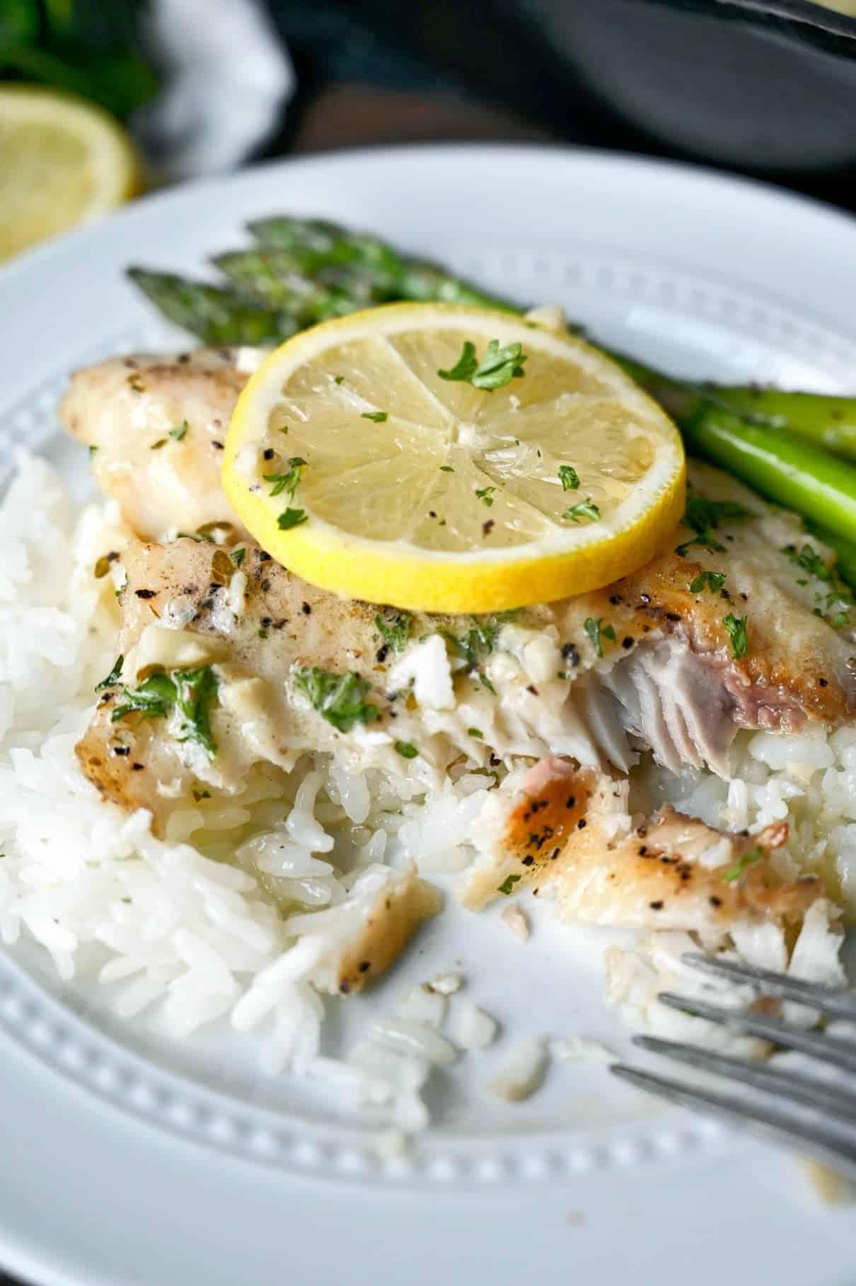 Tilapia tigaie pe orez cu sos de lămâie și deasupra o pană de lămâie.  Câteva mușcături mâncate și o furculiță așezată pe farfurie.