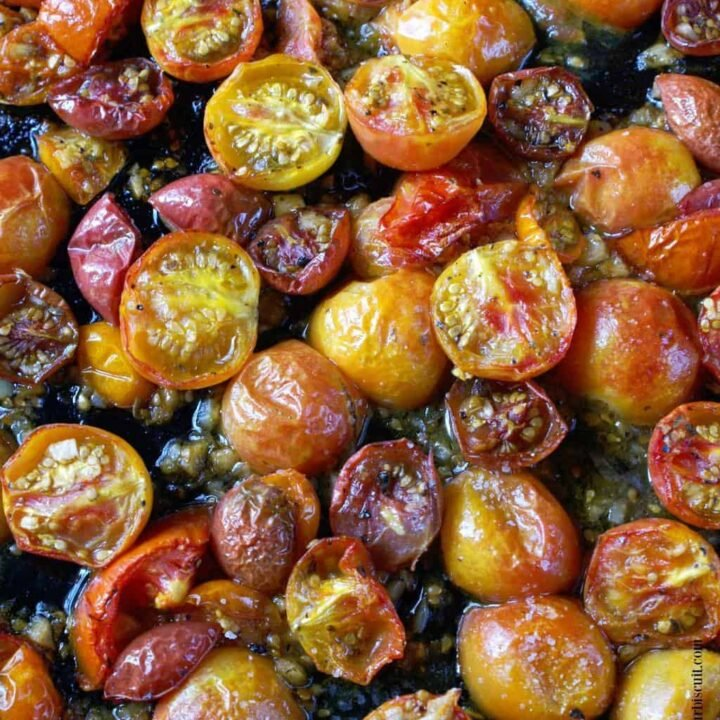 Garlic roasted cherry tomatoes on a baking sheet