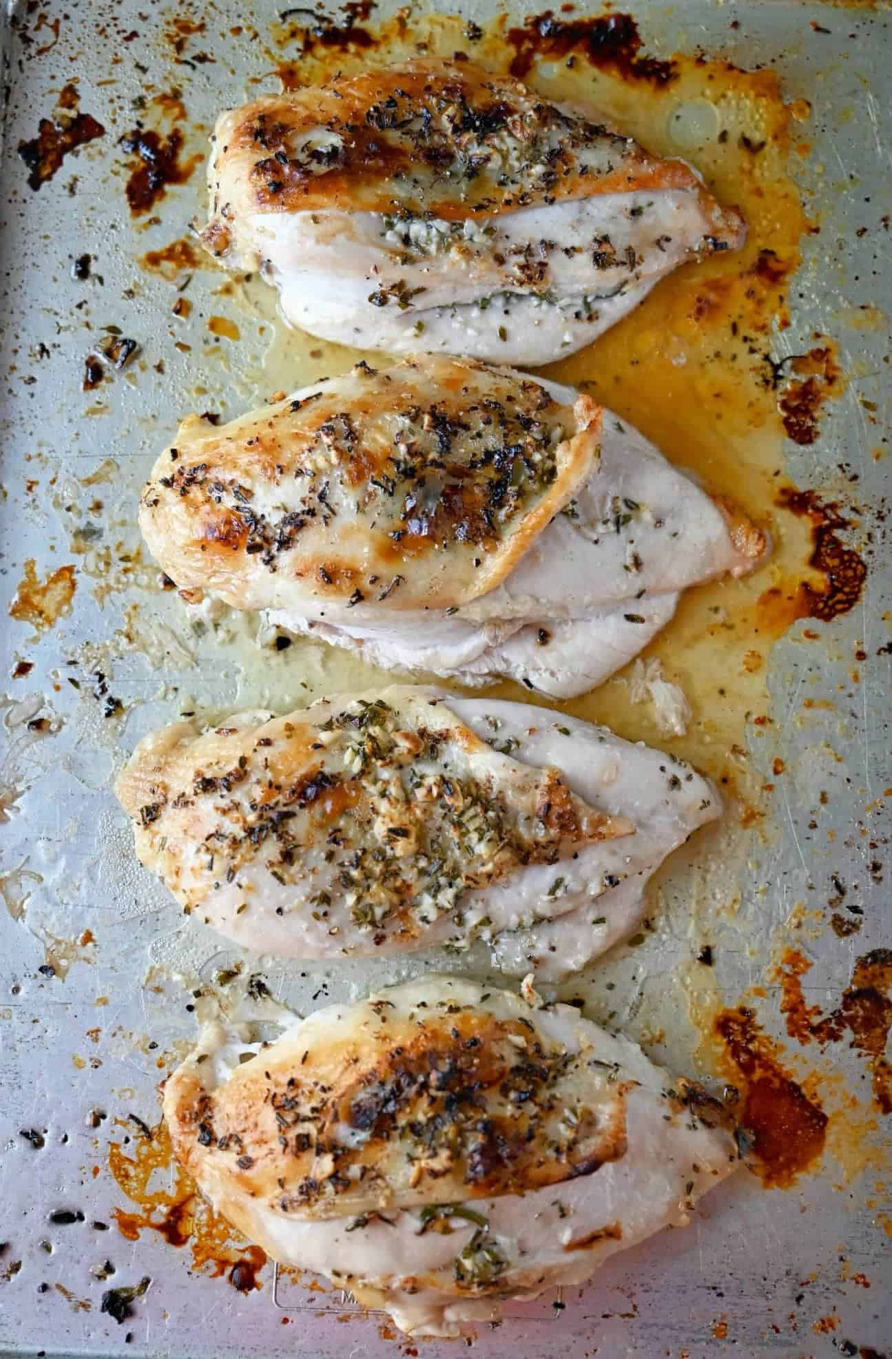 Four roasted chicken breasts on a baking sheet.