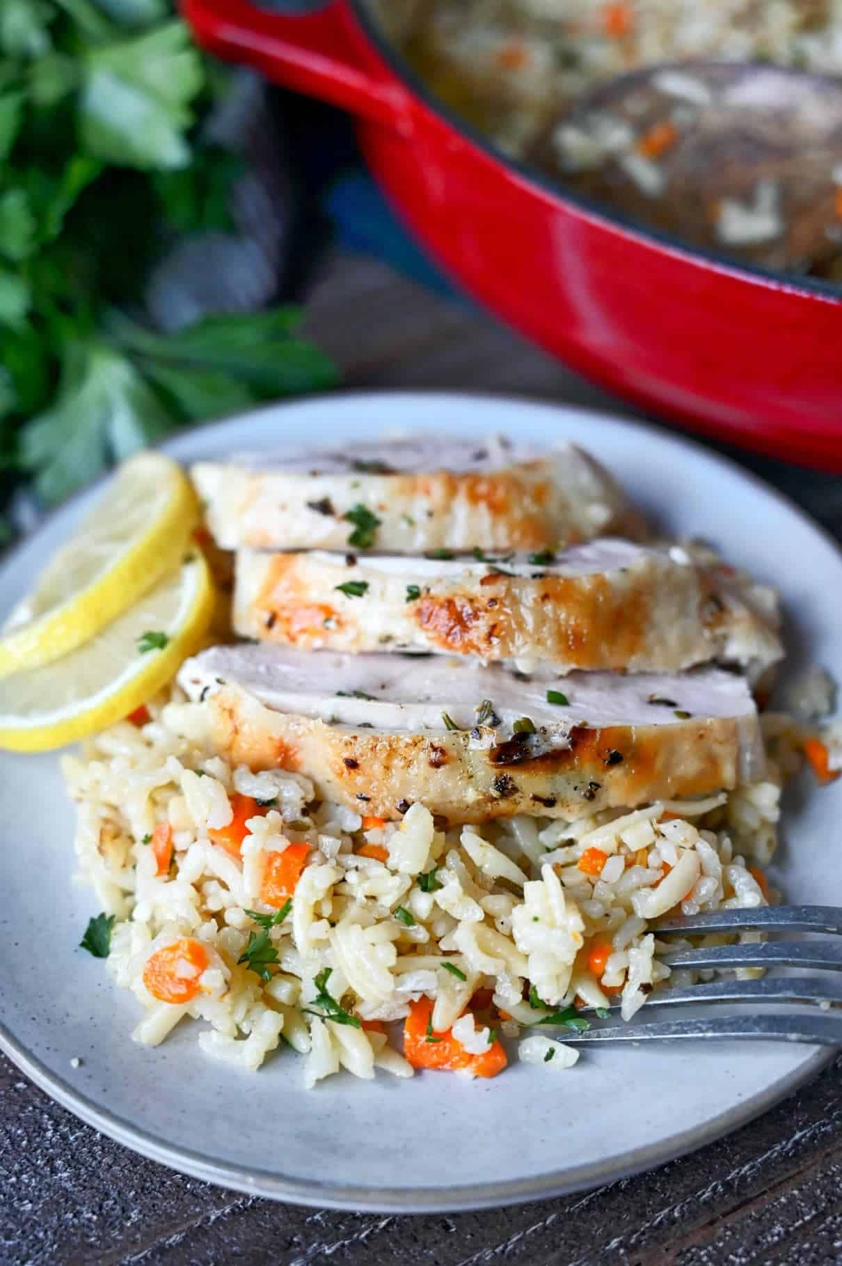 Lemon herb chickn sliced on a scoop of rice pilaf on a white plate.