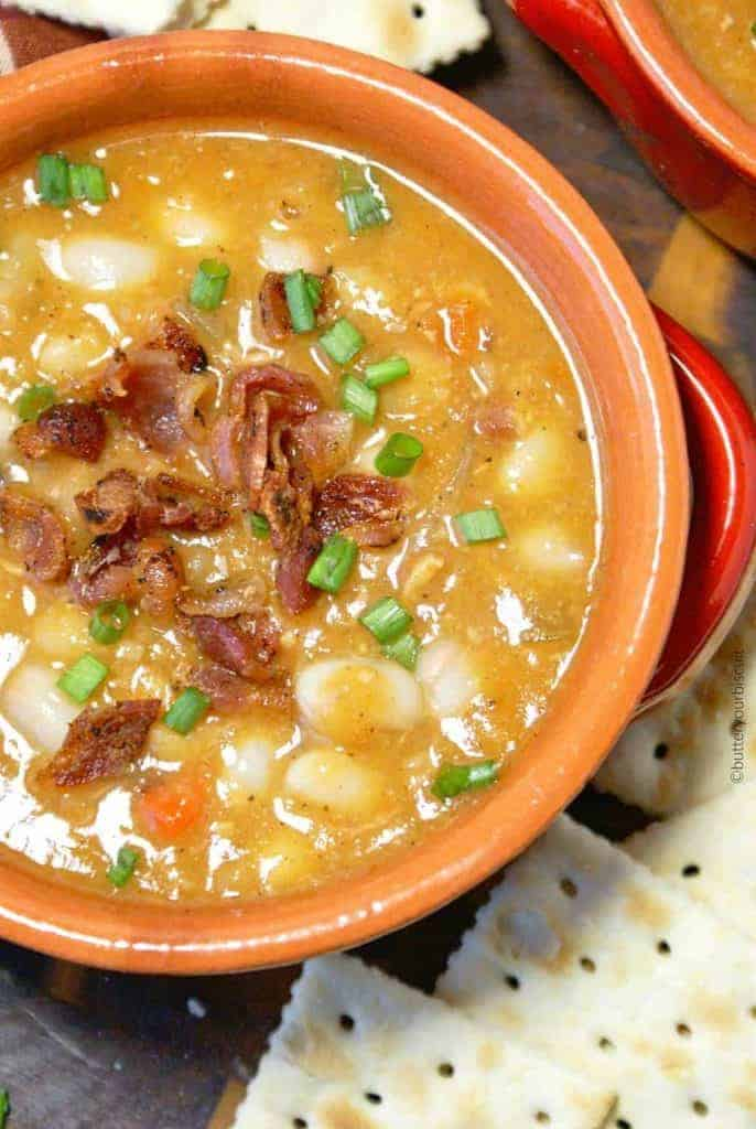 Slow cooker bean and bacon soup in a orange bowl.