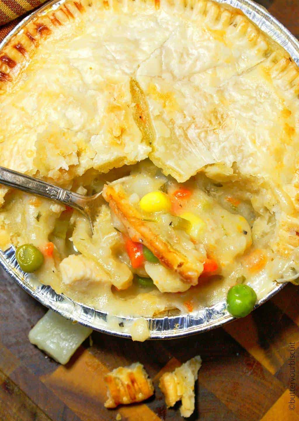 A mini chicken pot pie with a spoon eating a bite out.
