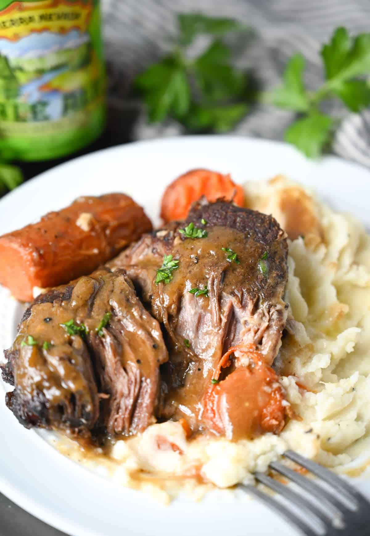 Slow cooker pot roast, mashed potatoes and roasted carrots on a white plate.