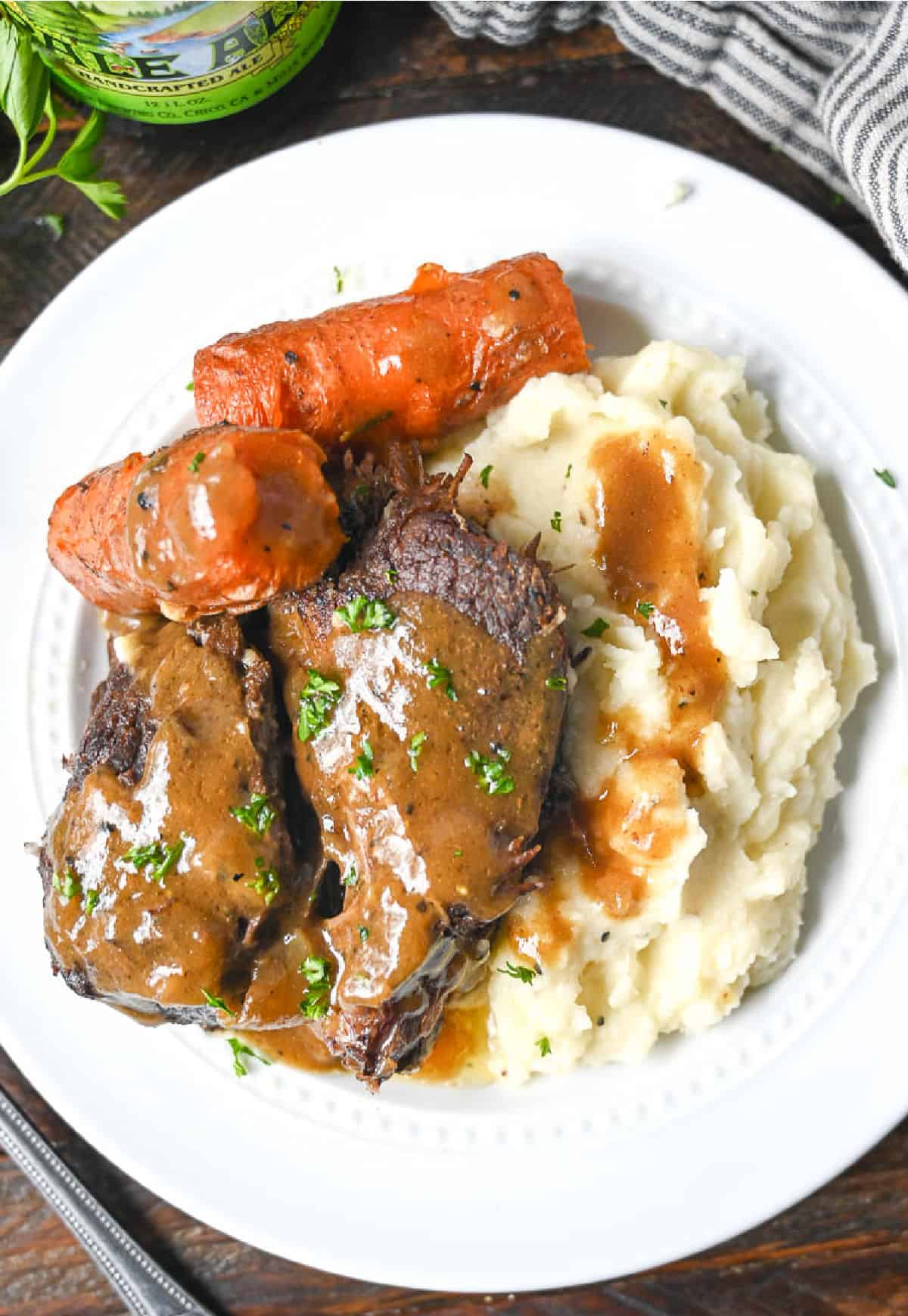 A white plate with mashed potatoes, pot roast, gravy and roasted carrots.