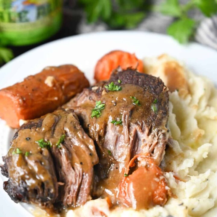 Pot roast on a white plate with mashed potatoes and roasted carrots,