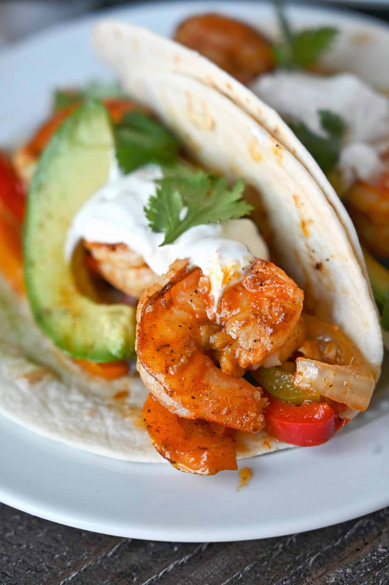 Cajun shrimp fajitas in a flour tortilla with a slice of avacado, sourcream and cilantro.