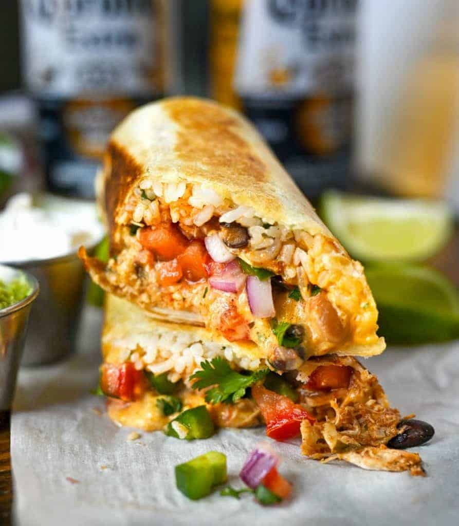 Slow cooker chicken burrito cut in half and stalked on top of each other.