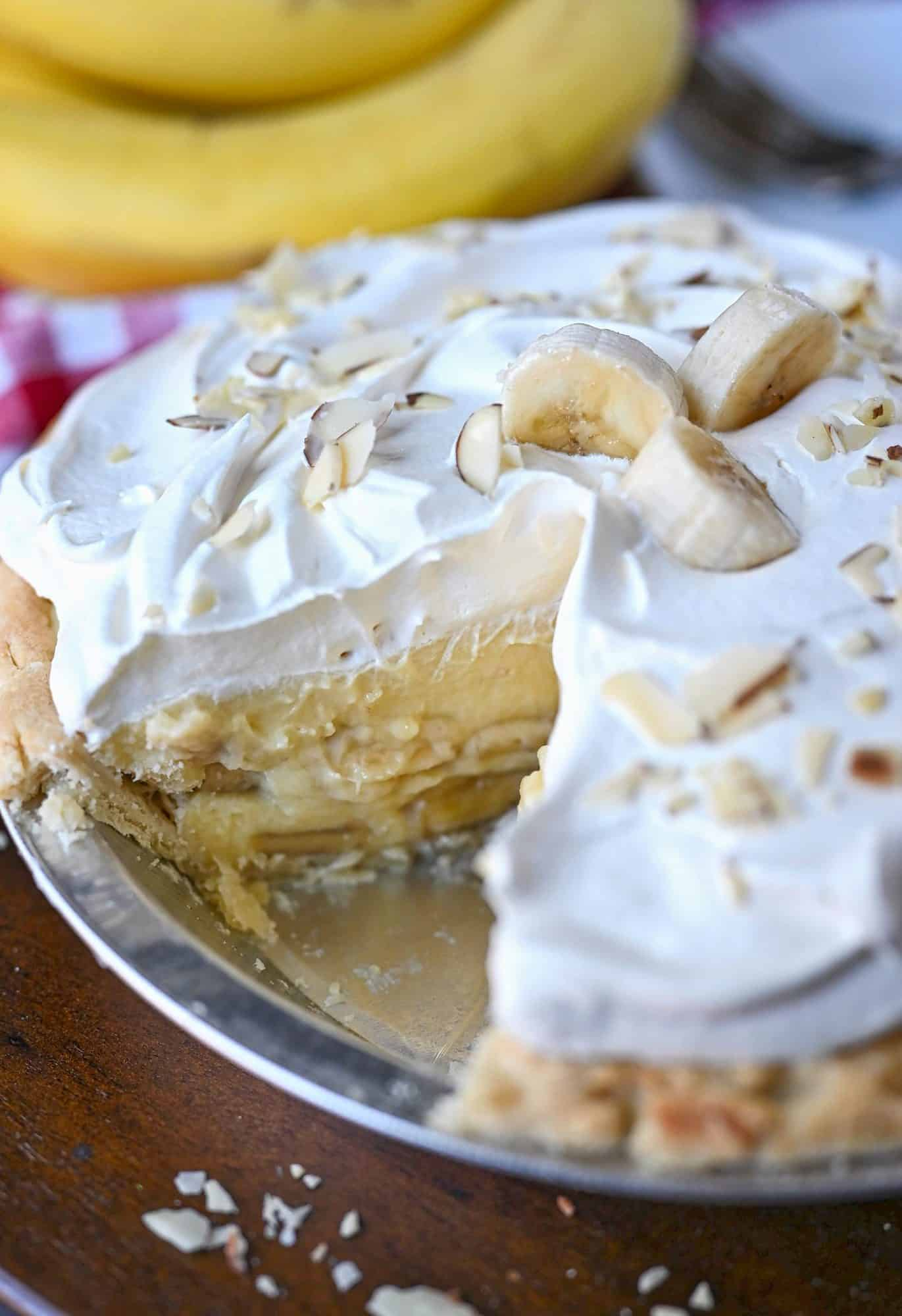 Whole banana cream pie with a slice cut out.