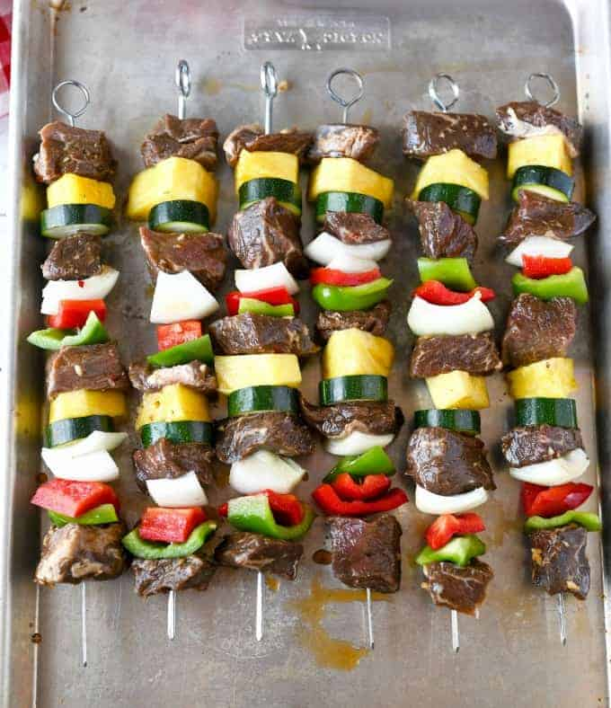 Six bebabs placed on a baking sheet and ready to place on the grill.
