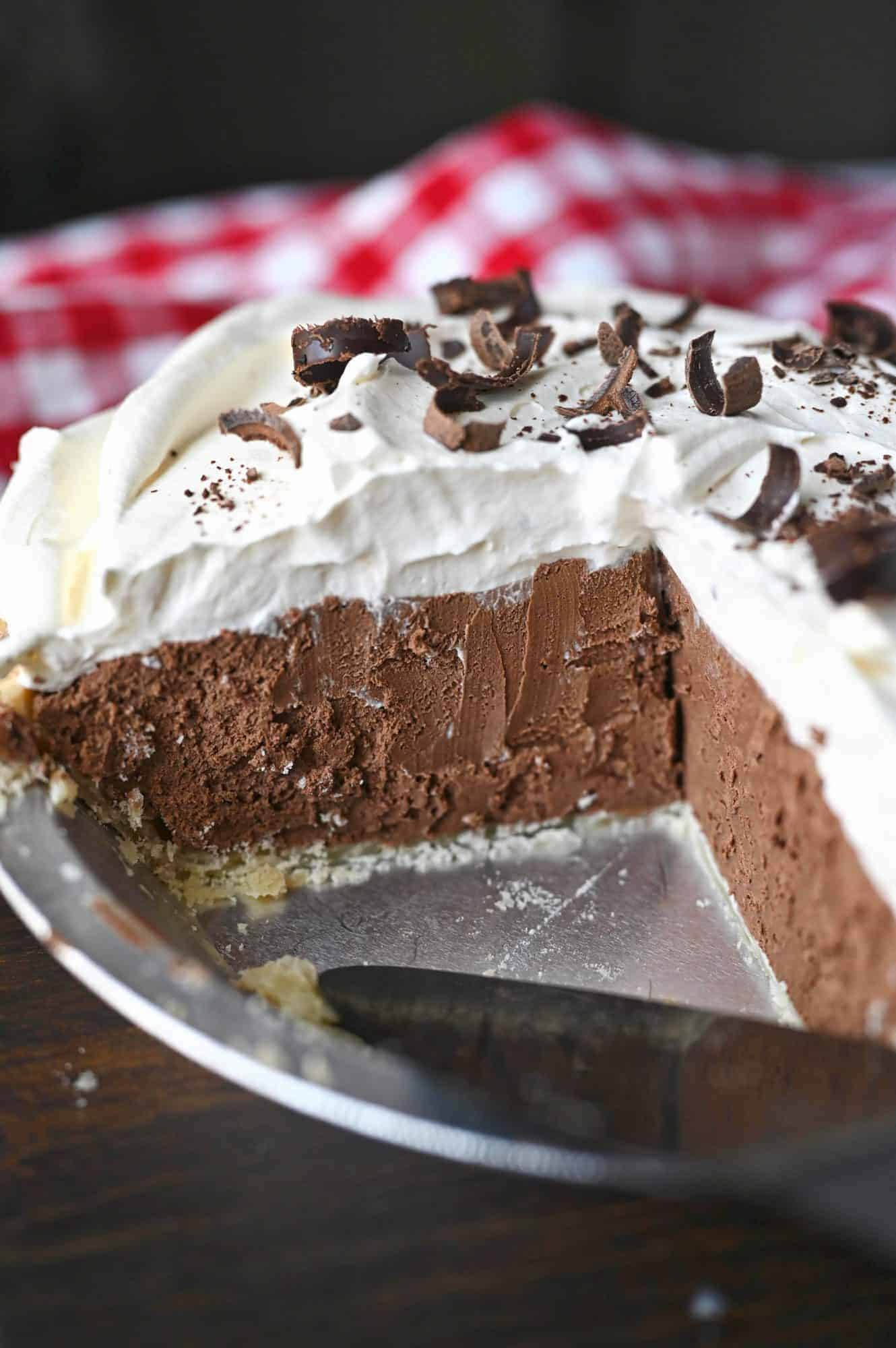 Chocolate cream pie in a pie dish with two slices removed.