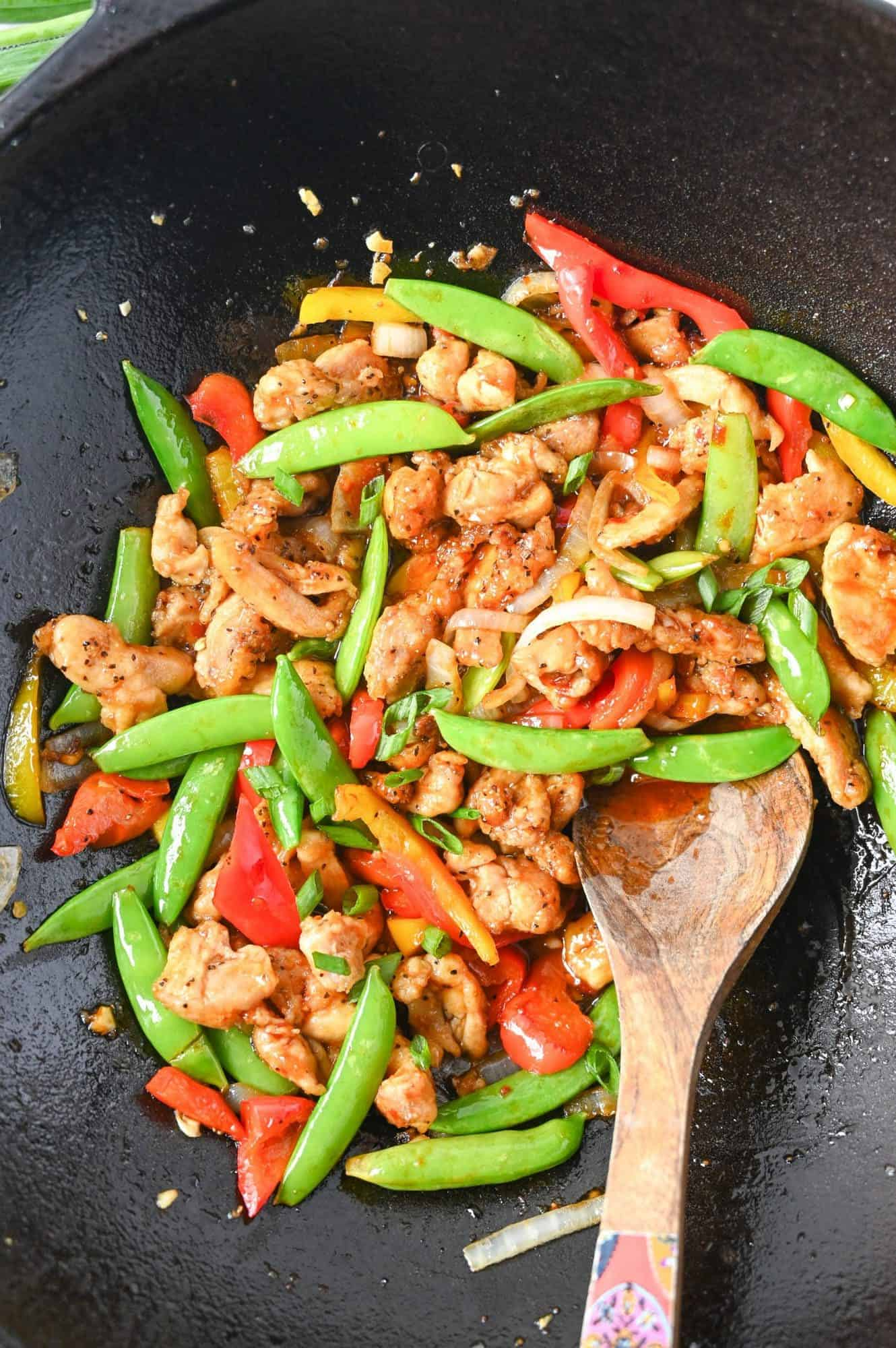 Sweet n spicy chicken stir fry in a cast iron wok and a wooden spoon.