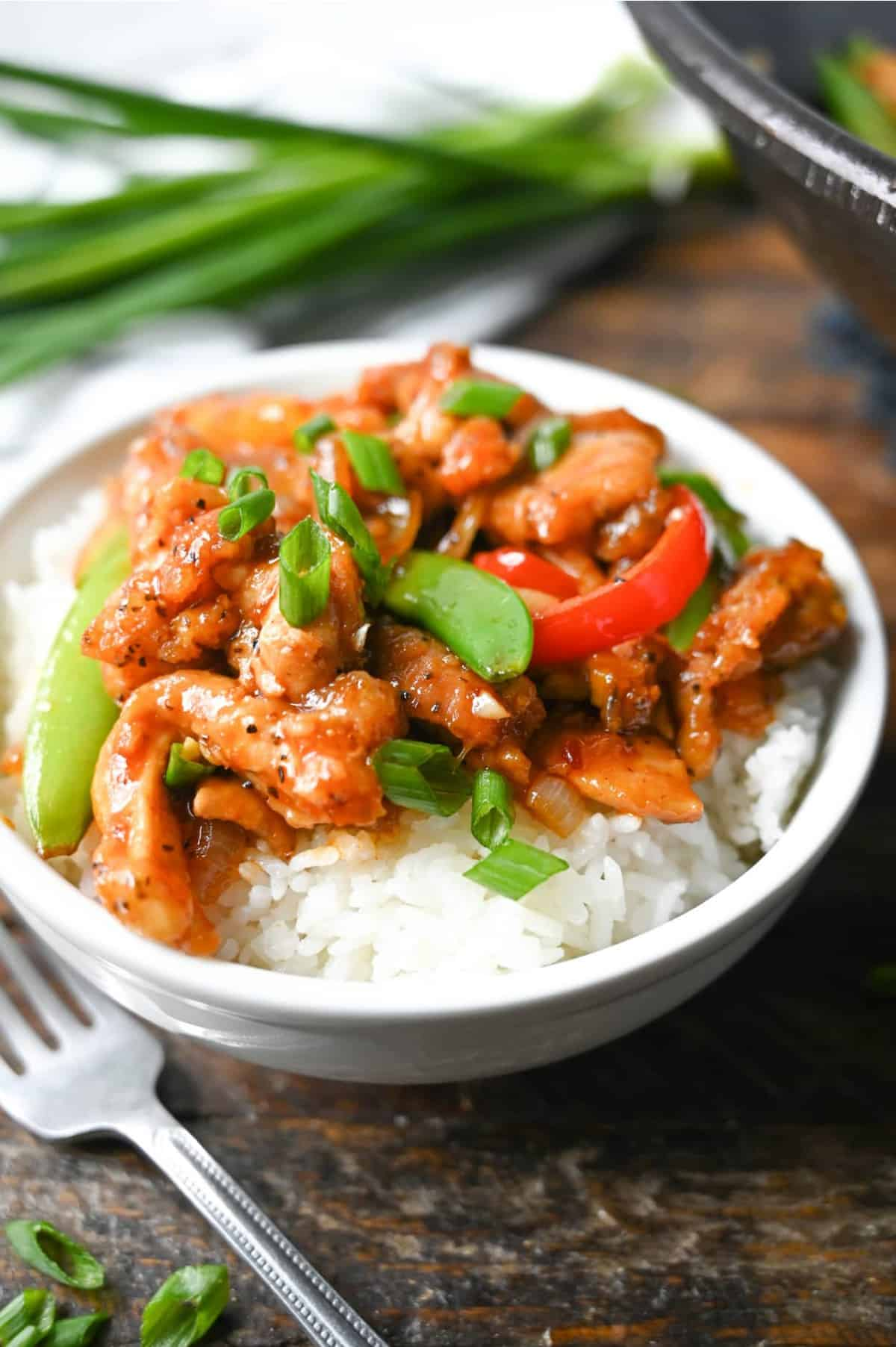 Sweet n spicy chicken stir fry piled on white rice in a white bowl.