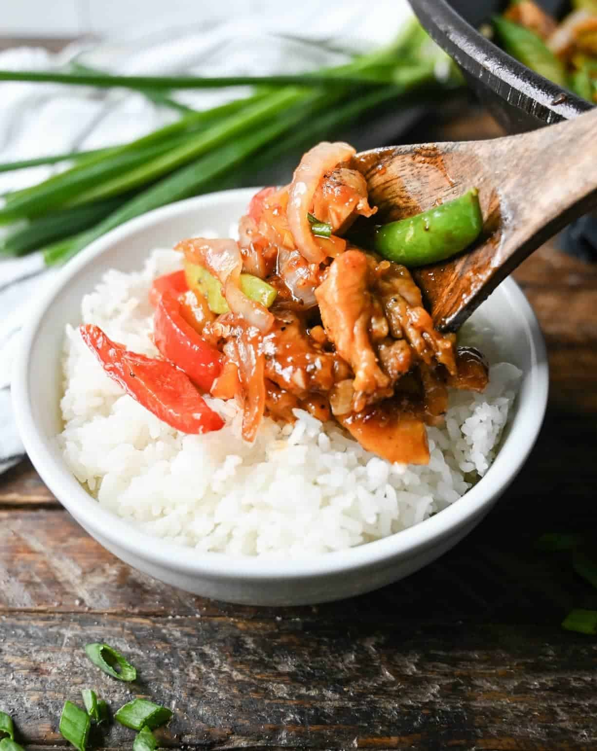 Sweet n spicy chicken stir fry served with a wooden spoon onto wgite rice.