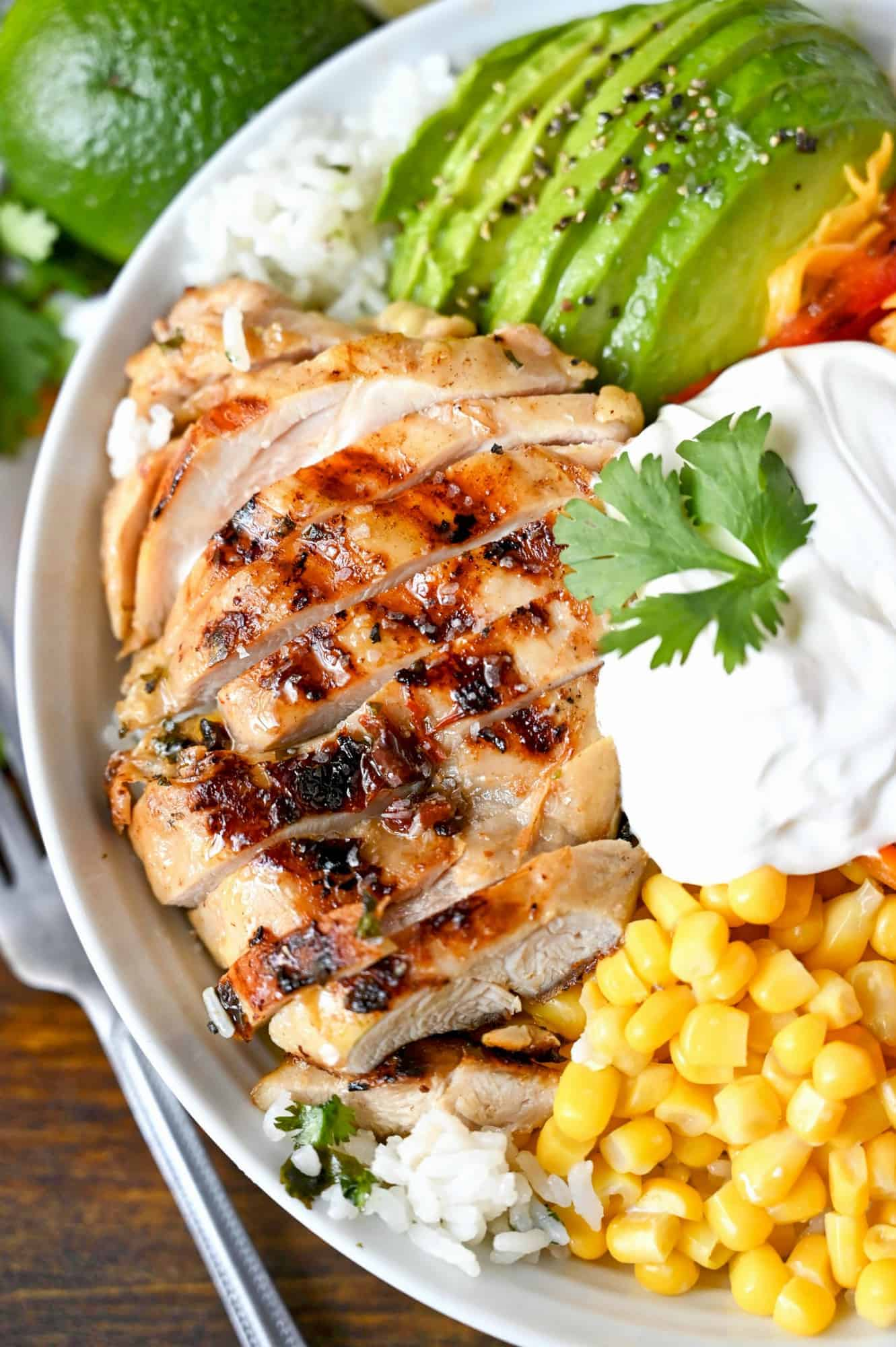 Tequila lime chicken, avacodo, cut into slices. Plus a scoop of corn and a some sour cream placed in a white bowl on top of cilantro rice.