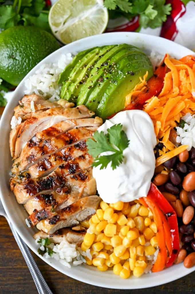 Tequila lime chicken, sliced avocado, scoop of corn, roasted red pepper slices, black beans. All piled on a bed of cilantro rice and a scoop of sour cream in a white bowl.