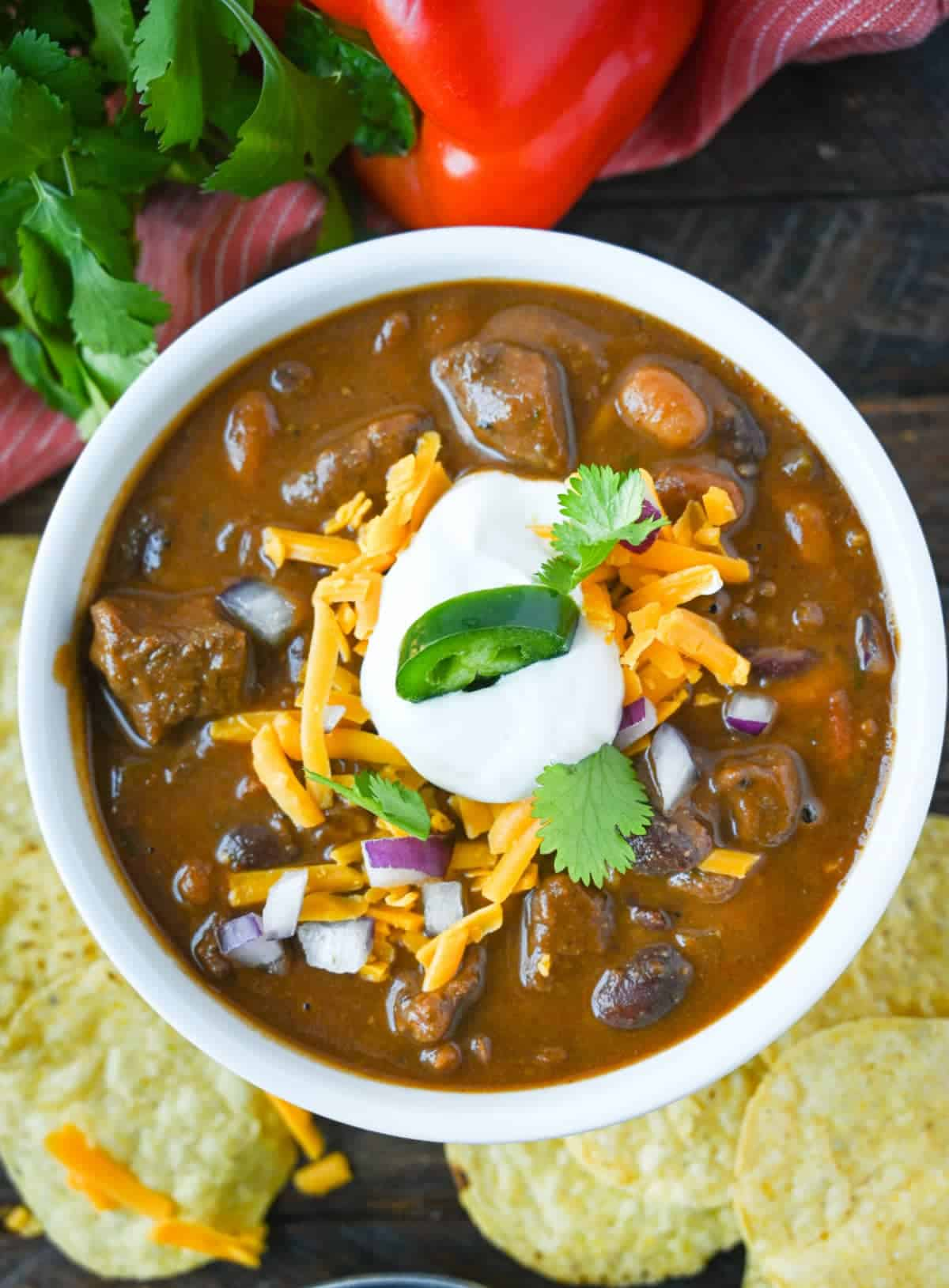 Steak chili with cshredded cheese, onions , sour cream and cilantro on top.