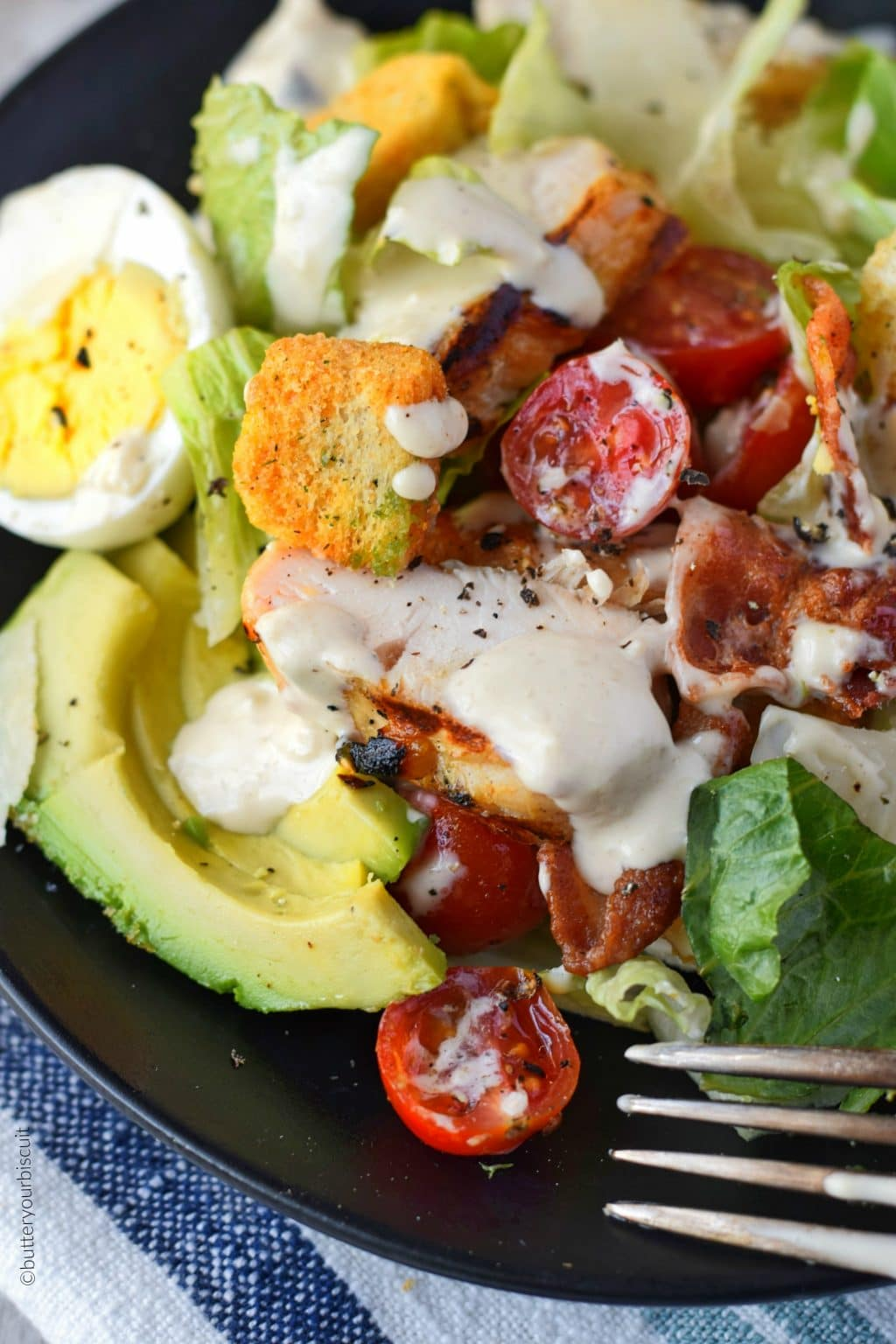 grilled chicken avocado salad on a black plate with a fork