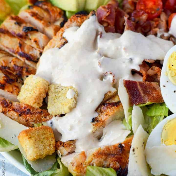 grilled chicken avocado caesar salad in a white bowl with caesar dressing