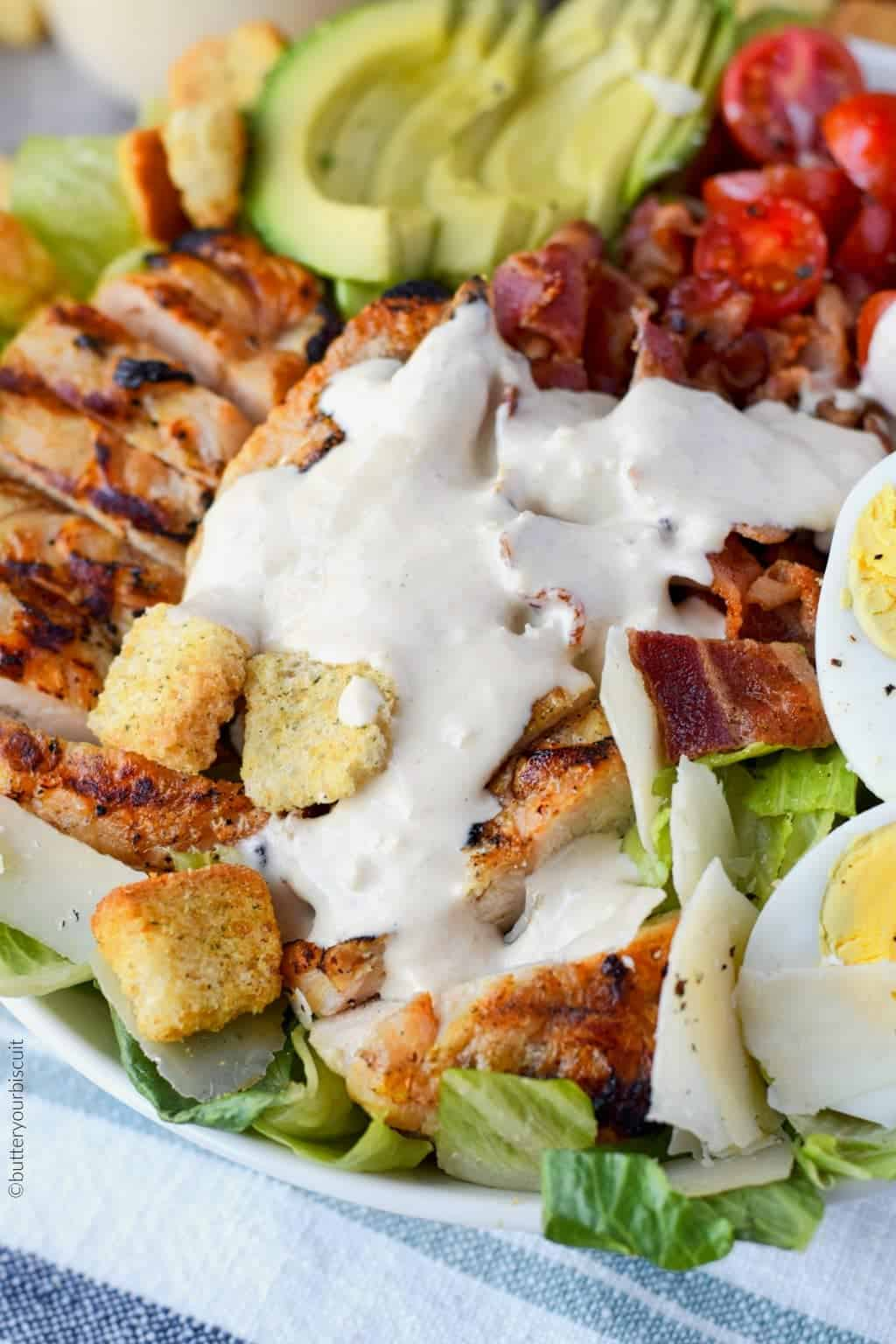grilled chicken avocado salad in a white bowl with caesar dressing