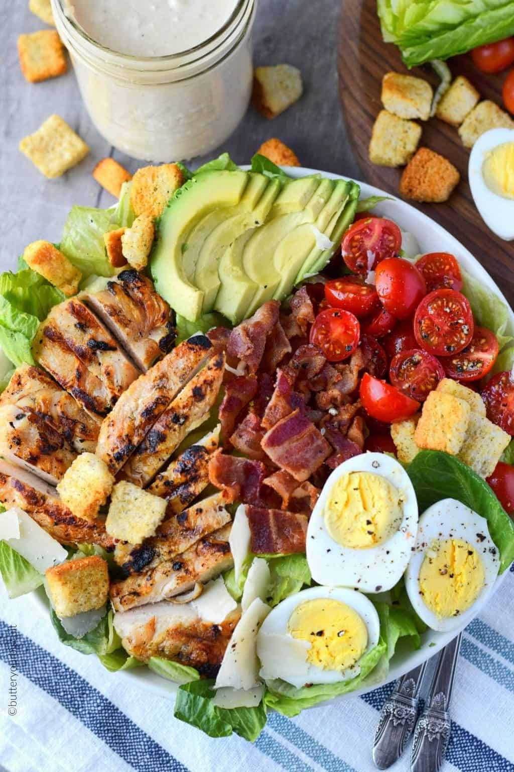 grilled chicken avocado salad in a white bowl