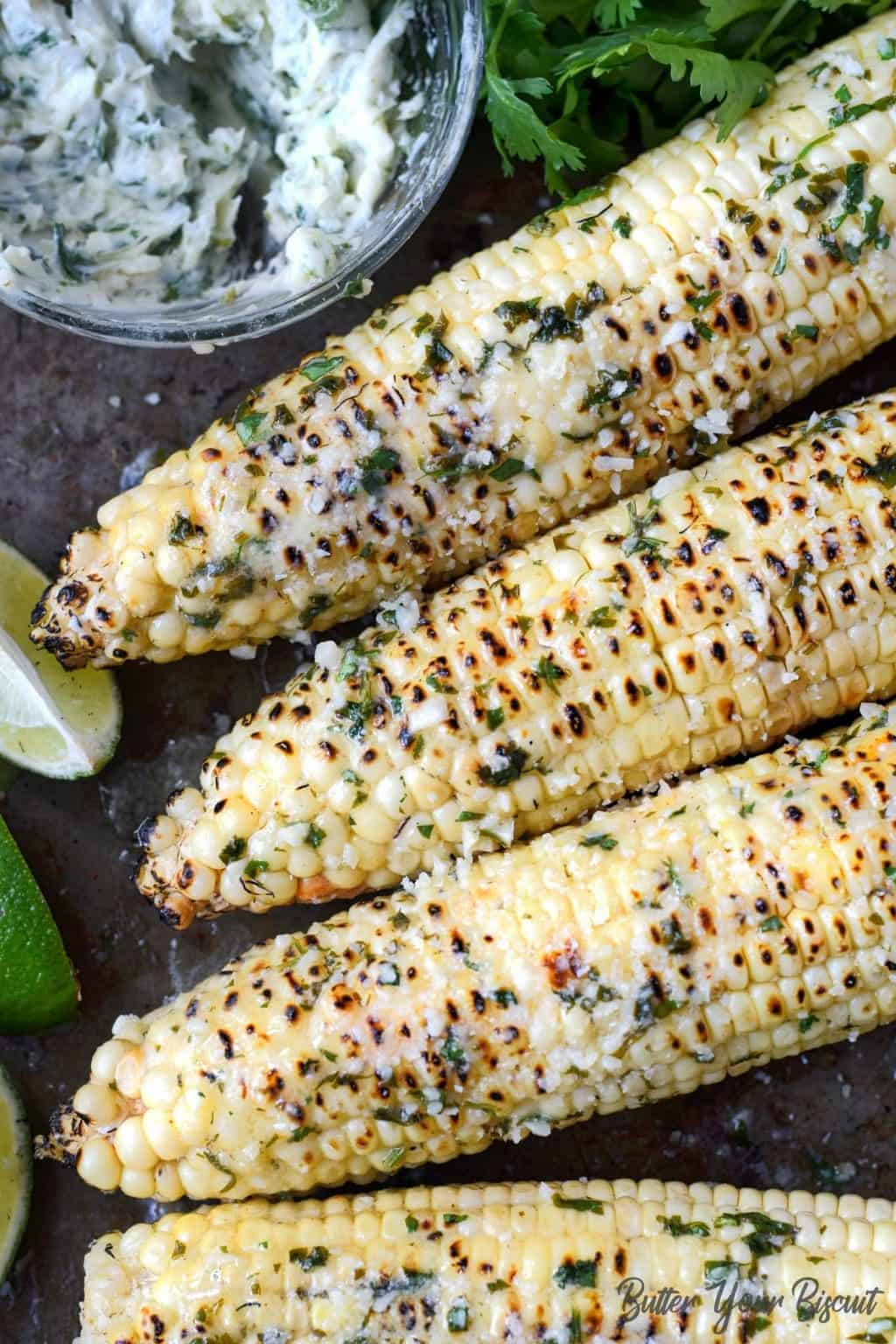 Four ears of grilled corn with melted butter on top.