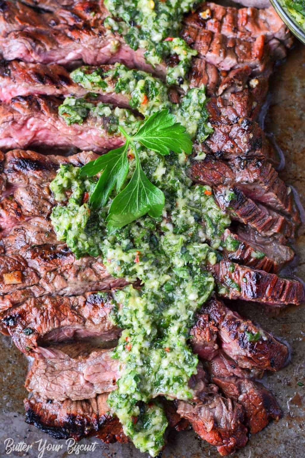 Grilled skirt steak and chimichurri sliced on a baking sheet