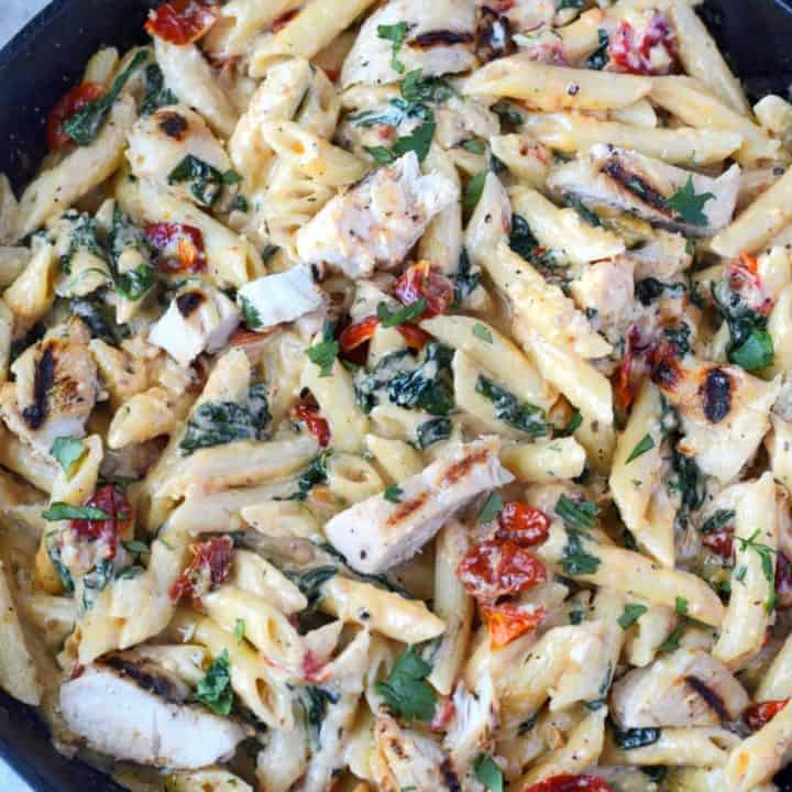 tuscan chicken pasta in a cast iron skillet