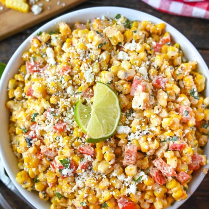Sweet corn salad in a large white bowl with corn on the cob on the side.