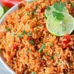 Restaurant style mexican rice in a white serving bowl with lime slices and cilantro on top