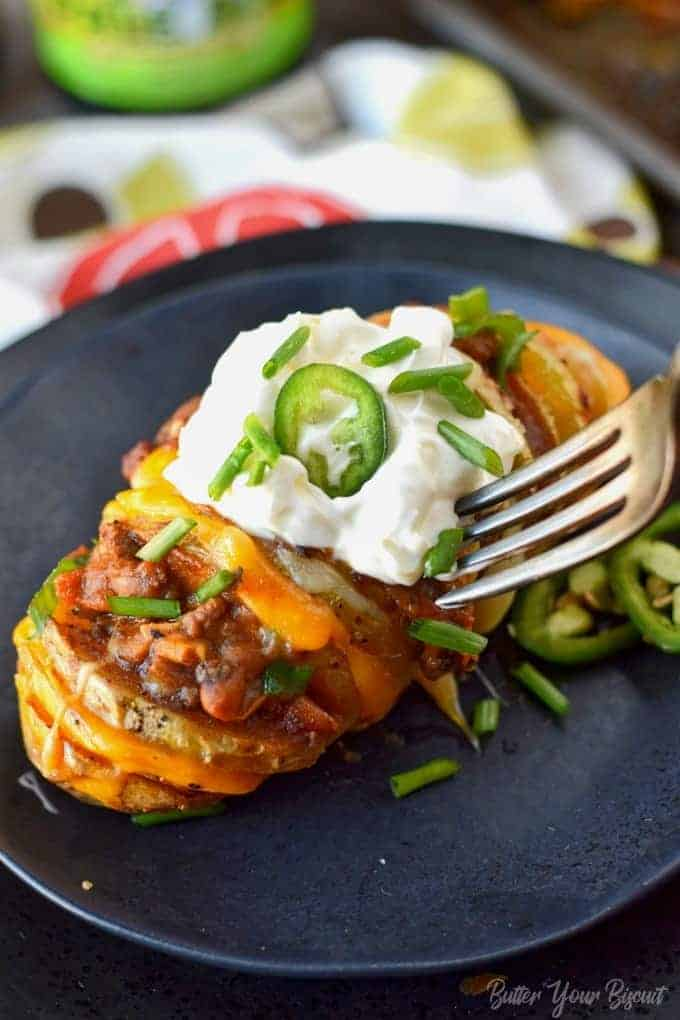 A hasselback potato stuffed with chili and cheese topped with sour cream and jalapeno slice.
