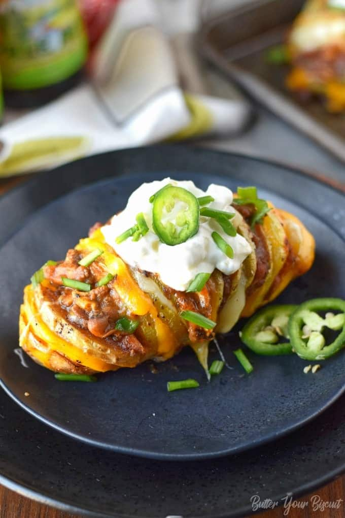A chili cheese stuffed hasselback potato with sour cream on a small bkack plate with a fork.