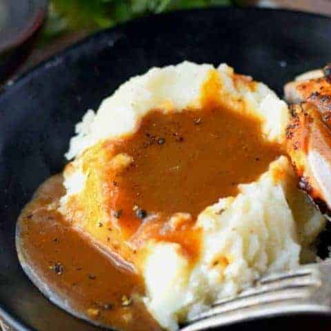 make ahead turkey gravy poured on some mashed potatoes on a black plate