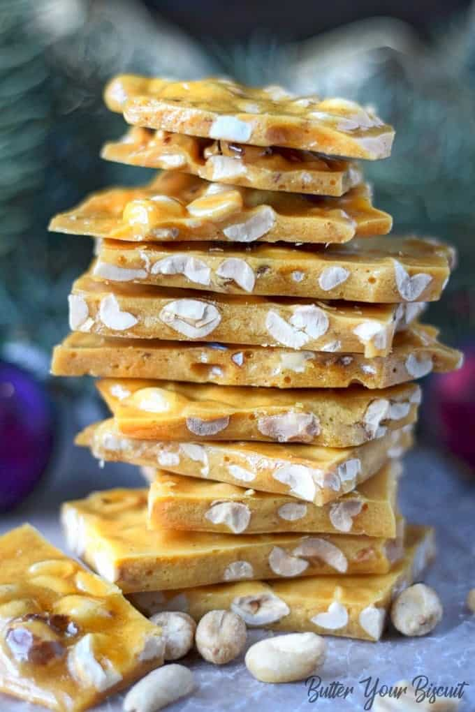 Stach of microwave peanut brittle in front of a christmas tree.
