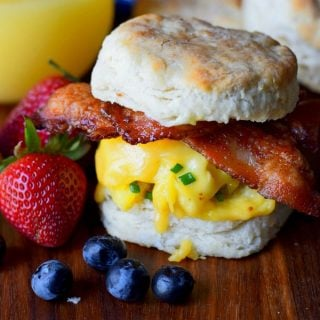 bacon egg and cheese biscuit sandwich on a cutting board with blueberries and strawberries and orange juice
