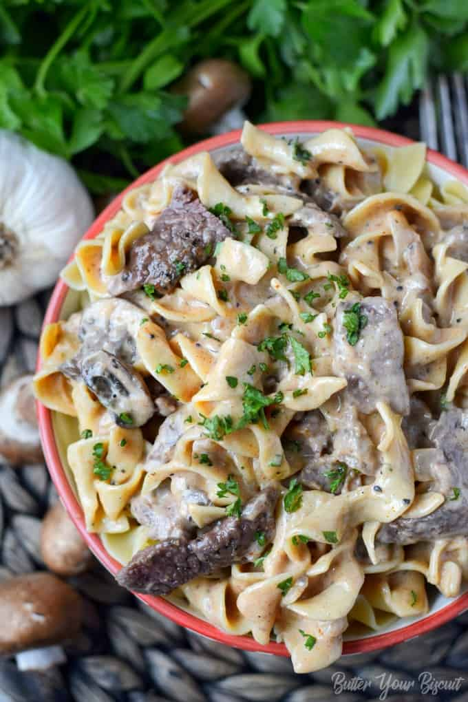 A photo of beef stroganoff in a bowl with fresh chopped parsley on top.