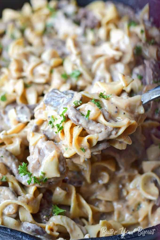 A serving spoon scooping out a serving of beef stroganoff.