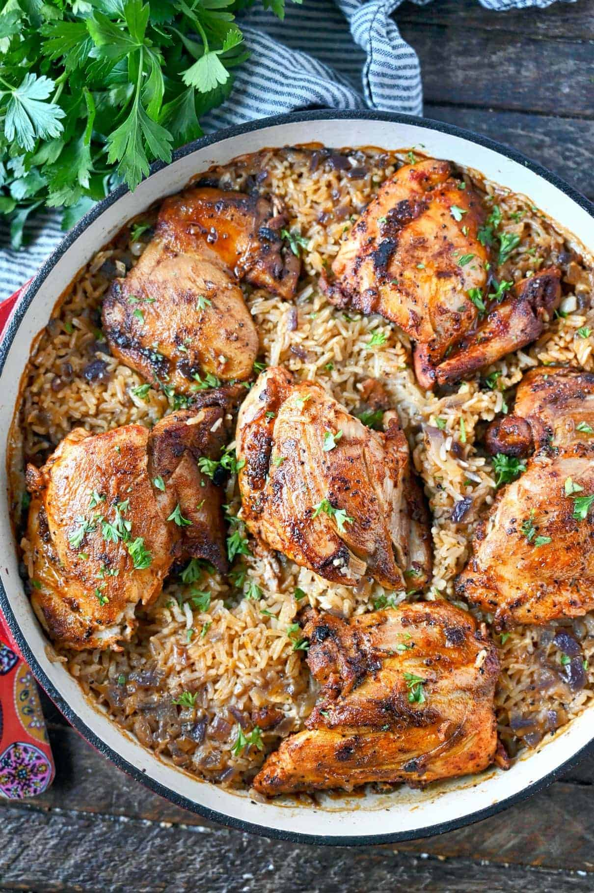 Six paprika chicken thighs in a bed of rice in a red skillet.