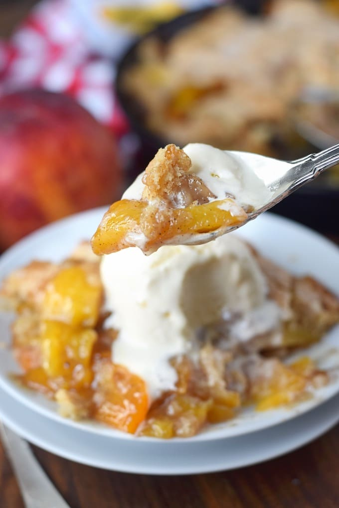 A spoon scooping a bite out of the peach cobbler with vanilla ice cream.