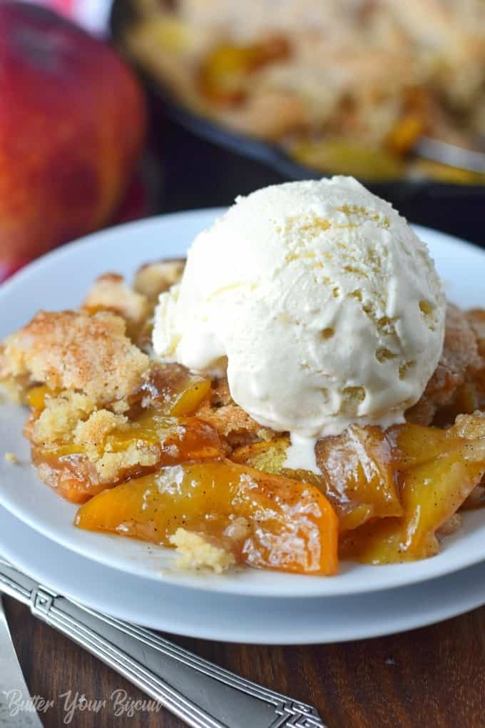 A scoop of peach cobbler with a scoop of vanilla ice cfeam on top.