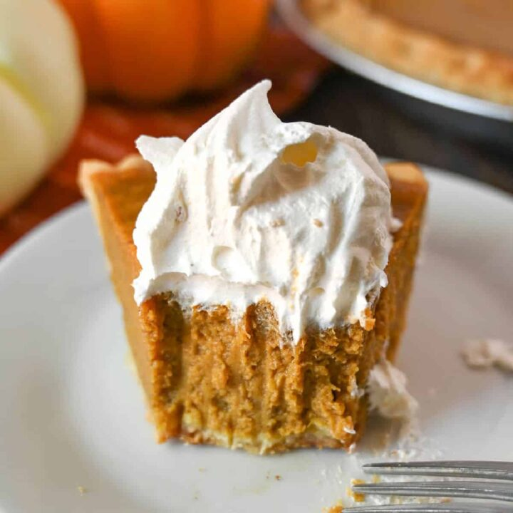 A slice of buttermilk pumpkin pie with a bute out of it.