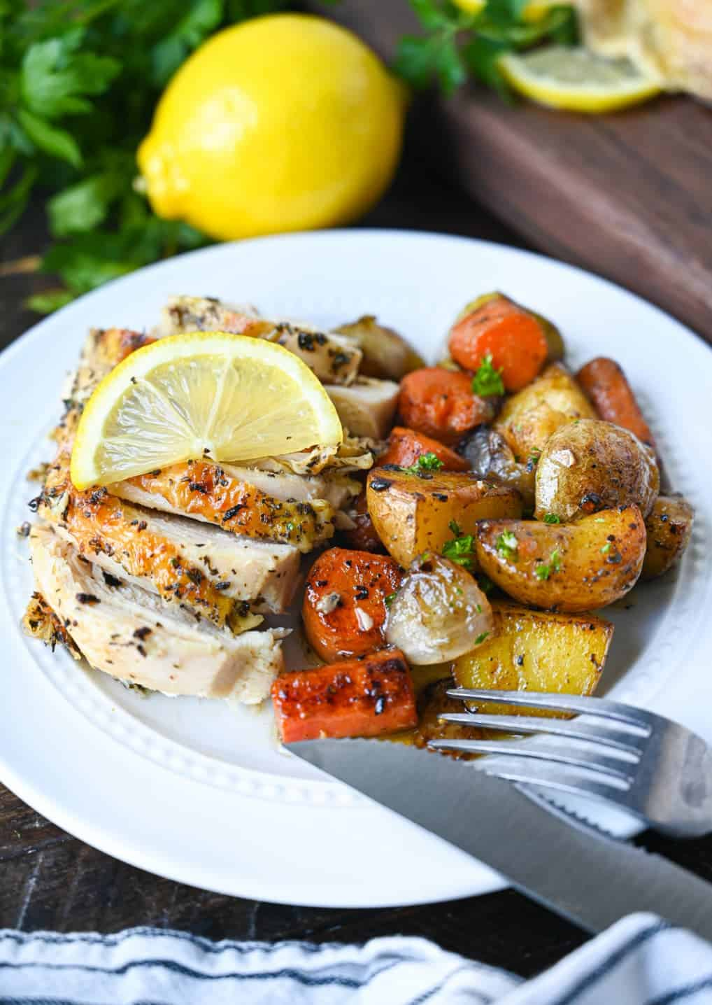 Sliced lemon galic chicken breast with a side of potatoes and carrots.