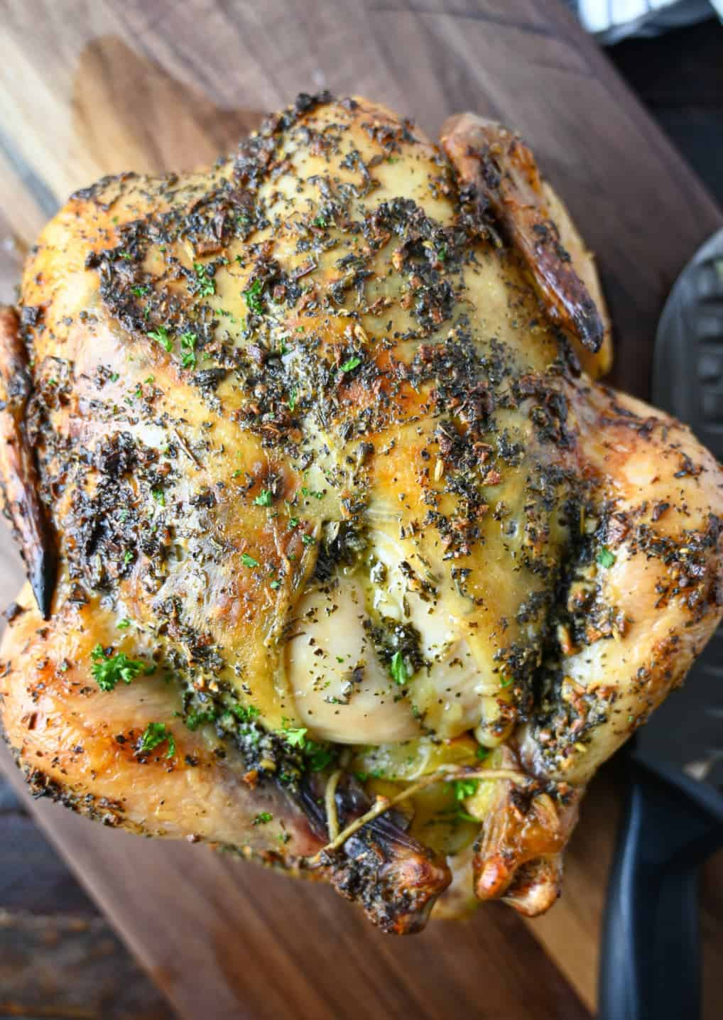 A whole lemon garlic roasted chicken placed in a cutting board.
